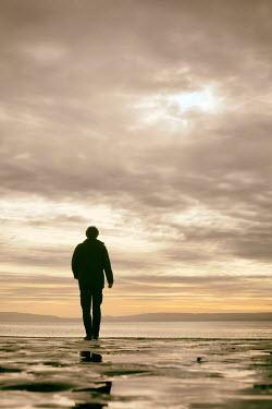 Tim Robinson SILHOUETTED MAN WALKING ON BEACH IN WINTER Men