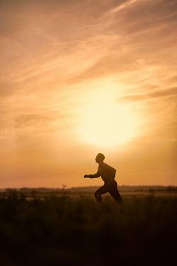 Magdalena Russocka man running in field at sunset Men