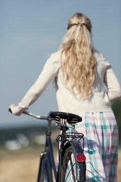 Magdalena Russocka retro blonde woman with bike walking in field