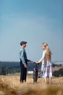 Magdalena Russocka retro couple with bike standing in field