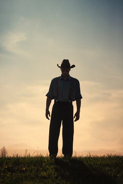 Magdalena Russocka man wearing cowboy hat standing on hill at sunset