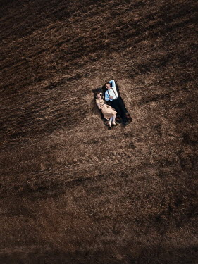 Magdalena Russocka retro couple lying on picnic blanket in field from above