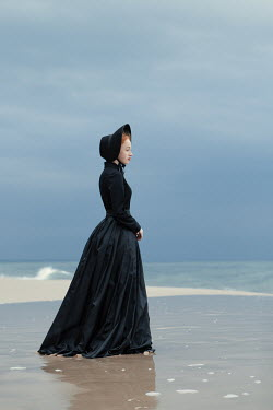 Magdalena Russocka historical woman in black dress and bonnet standing on sandy beach