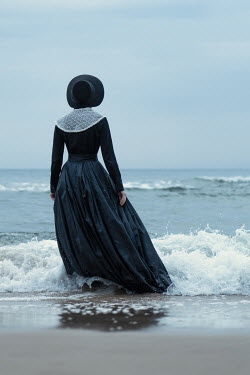 Magdalena Russocka historical woman in black dress and bonnet going into sea