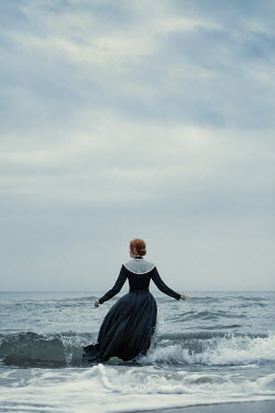 Magdalena Russocka historical woman in black dress going into sea