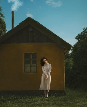 Svitozar Bilorusov WOMAN STANDING OUTSIDE CABIN IN SUMMER Women
