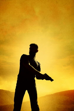 Magdalena Russocka SILHOUETTED MAN WITH GUN OUTDOORS AT SUNSET Men