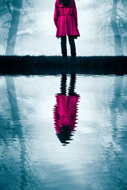 Magdalena Russocka modern  woman in pink coat standing in woods reflected in water