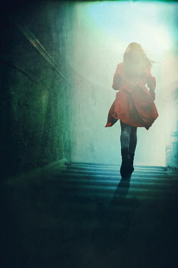 Magdalena Russocka modern woman in red coat running up stairs in old house