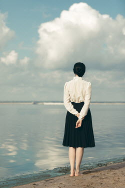 Dorota Gorecka BAREFOOT WOMAN IN WHITE BLOUSE STANDING BY SEA Women