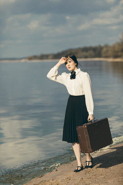 Dorota Gorecka WOMAN CARRYING SUITCASE ON SANDY BEACH Women
