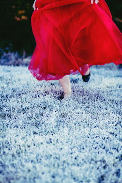 Marie Carr WOMAN IN RED DRESS RUNNING IN FROSTY GARDEN Women