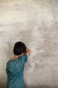 Mohamad Itani SAD LITTLE BOY LEANING ON CONCRETE WALL Children