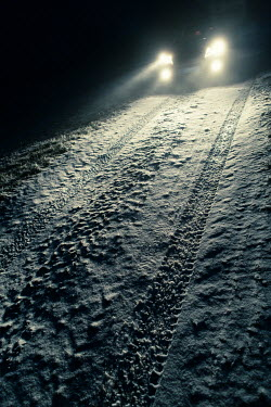 Magdalena Russocka close up of car with headlights on snowy country road