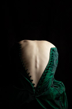 Natasza Fiedotjew bare back of young woman curled up in unbuttoned historical dress