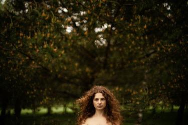 Alexandra Bochkareva BRUNETTE WOMAN STANDING BY TREES IN COUNTRYSIDE Women
