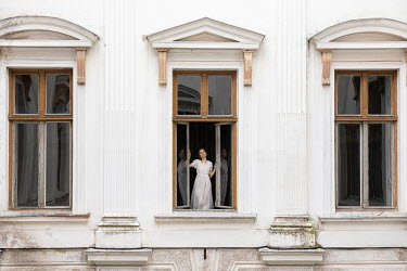 Dorota Gorecka GIRL STANDING AT WINDOW OF GRAND HOUSE Women