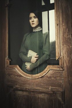 Dorota Gorecka WOMAN STANDING HOLDING BOOK BY GLASS DOOR Women