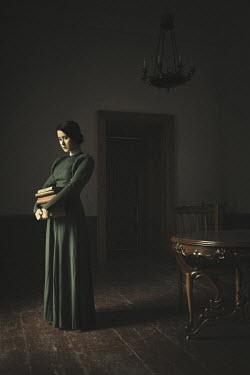 Dorota Gorecka WOMAN STANDING HOLDING BOOKS IN HOUSE Women