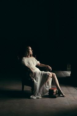Dorota Gorecka BAREFOOT WOMAN SITTING WITH BOOKS IN DARK HOUSE Women