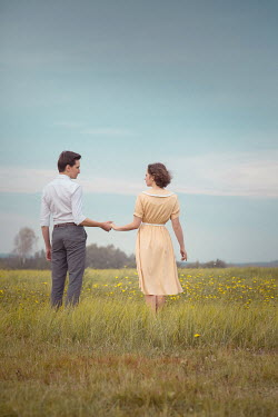 Joanna Czogala RETRO COUPLE HOLDING HANDS IN FIELD Couples