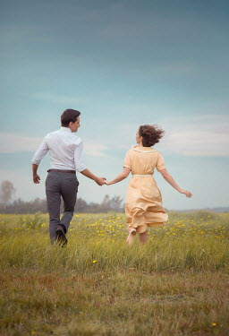 Joanna Czogala RUNNING RETRO COUPLE HOLDING HANDS IN FIELD Women