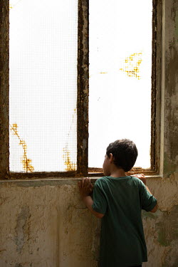 Mohamad Itani LITTLE BOY IN DERELICT BUILDING WATCHING AT WINDOW Children
