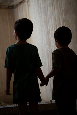 Mohamad Itani TWO LITTLE BOYS HOLDING HANDS IN SHABBY BUILDING Children