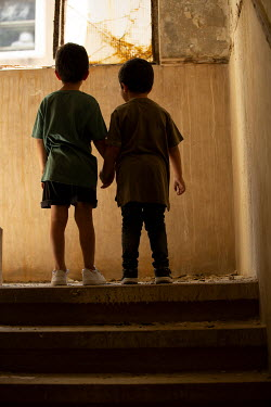 Mohamad Itani TWO LITTLE BOYS HOLDING HANDS IN DERELICT BUILDING Children