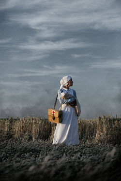 Magdalena Russocka wartime nurse holding infant baby standing in field