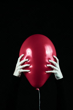Magdalena Russocka close up of female's hands squeezing red balloon