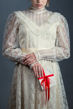 Magdalena Russocka historical woman in lace dress with bundle of letters with red ribbon