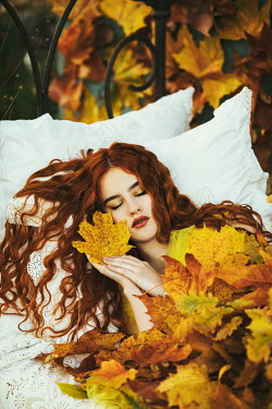 Jovana Rikalo WOMAN WITH RED HAIR IN BED WITH LEAVES OUTDOORS Women