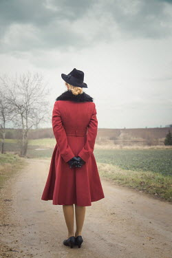 Joanna Czogala Young woman in 1940s red coat standing on rural road