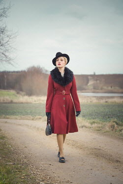 Joanna Czogala Young woman in 1940s red coat walking on rural road