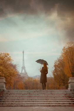 Drunaa Young woman with umbrella in park during autumn in Paris, France