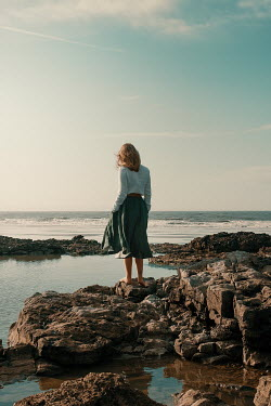 Rekha Garton Young woman standing on rocks by sea
