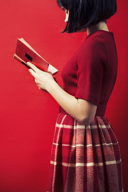 Robin Macmillan Young woman reading in checked red skirt and blouse