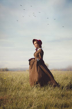 Joanna Czogala Young woman in Victorian dress and bonnet standing in field