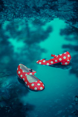 Joanna Czogala Discarded polka dot woman's shoes in puddle