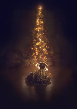 Jessica Drossin Girl sitting by illuminated Christmas tree
