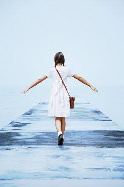 Kerstin Marinov Girl in white dress walking on jetty