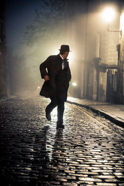 Laurence Winram Man in hat and coat walking on cobblestone street at night