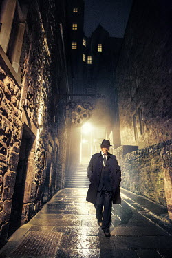 Laurence Winram Man in hat and coat walking on steps at night