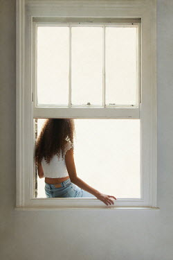 Miguel Sobreira Young woman sitting on window sill
