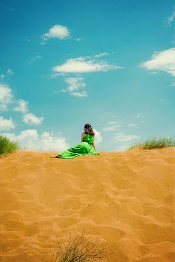 Svetlana Bekyarova Young woman in green dress sitting on sand dunes
