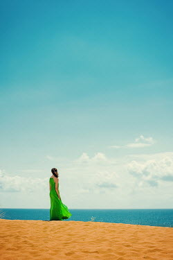 Svetlana Bekyarova Young woman in green dress standing on sand dunes