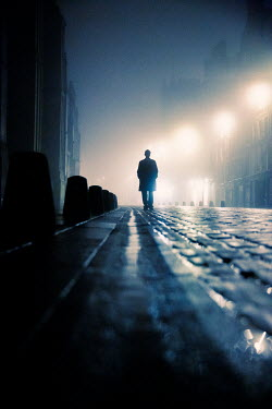 Laurence Winram SILHOUETTED MAN WALKING IN CITY STREET AT NIGHT Men
