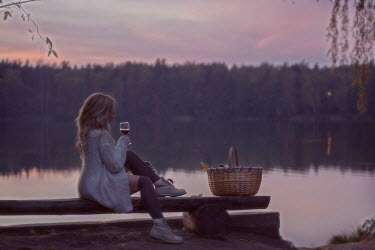 Andreeva Svoboda Young woman in sweater sitting by lake at sunset
