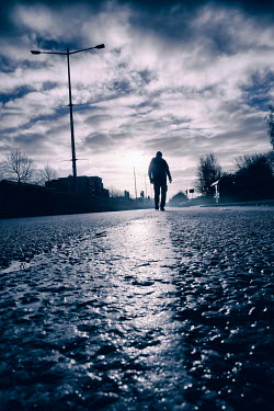 Tim Robinson Silhouette of man walking on road